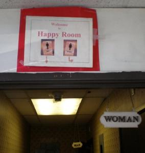 Sign to happy room above toilets